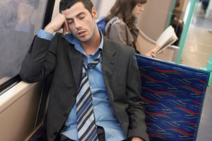 A man asleep on the train with tie unfastened